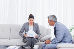 Stressed businesswoman holding documents and businessman trying Stock Photo
