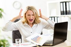 Stressed businesswoman at laptop in office Royalty Free Stock Images