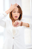 Stressed businesswoman looking at wrist watch Royalty Free Stock Photo