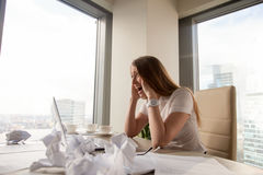 Stressed businesswoman screaming at workplace. Stressed businesswoman screaming at  desk covered crumpled paper. Female entrepreneur feeling strong nervous Stock Photography
