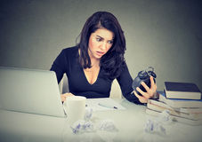 Stressed businesswoman sitting at her office desk pressured by lack of time. Stressed business woman sitting at her office desk pressured by lack of time Stock Photos