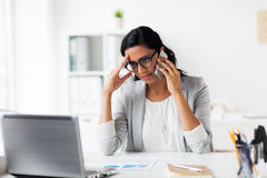 Stressed businesswoman with smartphone at office Royalty Free Stock Photography