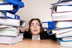 Stressed businesswoman with stack of folders Royalty Free Stock Image