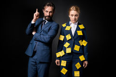Stressed businesswoman with sticky notes on clothes standing near bearded businessman pointing up with finger. Isolated on black Stock Photography