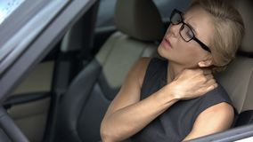 Stressed businesswoman suffering neck discomfort, sitting in car, sedentary life. Stock photo royalty free stock photos