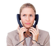 Stressed businesswoman tangled up in phone wires Royalty Free Stock Images