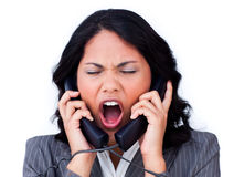 Stressed businesswoman tangled up in phone wires Royalty Free Stock Image