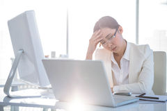 Stressed businesswoman working at her desk Stock Image