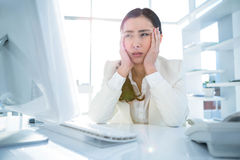 Stressed businesswoman working at her desk Stock Photo