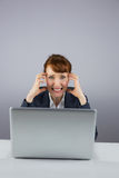Stressed businesswoman working on laptop Stock Image