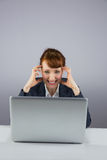 Stressed businesswoman working on laptop Stock Images