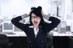 Stressed businesswoman at workplace Stock Photo