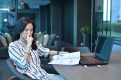Stressed Casual Business Asian Woman reading a book in front of Stock Image
