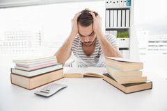 Stressed casual businessman studying at his desk Royalty Free Stock Photography