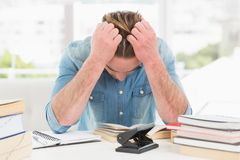 Stressed casual businessman studying at his desk Royalty Free Stock Photos