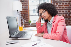 Stressed casual businesswoman sitting at desk Royalty Free Stock Photos