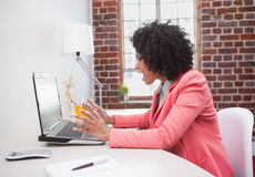 Stressed casual businesswoman sitting at desk Stock Images
