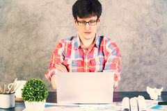 Stressed caucasian male crossed arms. Serious caucasian male with crossed arms sitting at office desk with plant and other items looking at a laptop screen Stock Photography
