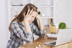 Stressed caucasian worker. Stressed caucasian female sitting at wooden office desk and looking at computer screen Royalty Free Stock Photos