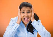 Stressed. Closeup portrait of worried, stressed, overwhelmed young woman, funny looking girl, covering her ears, screaming going crazy,  orange background. Human Stock Photo