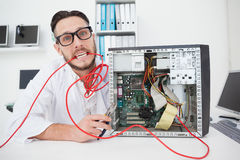 Stressed computer engineer working on broken cables. In his office Royalty Free Stock Photos