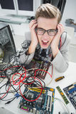 Stressed computer engineer working on broken cables. In his office Royalty Free Stock Photography