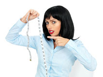 Stressed and Concerned Young Woman Holding and Reading Off a Tape Measure Stock Photography
