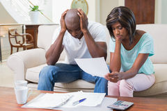 Stressed couple calculating bills on the couch Royalty Free Stock Images