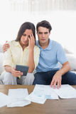 Stressed couple doing their accounts. Sat on a couch royalty free stock photos