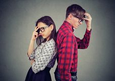 Stressed couple with hand on head standing back to back looking down in frustration royalty free stock photos