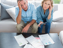 Stressed couple sitting on their couch paying their bills. Smiling at camera at home in the living room Royalty Free Stock Photography
