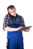 Stressed craftsman with digital tablet and mobile phone Stock Photos