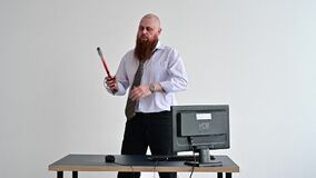 Stressed crazy businessman smashing his computer in office using ax problem concept. The man has problems at work and