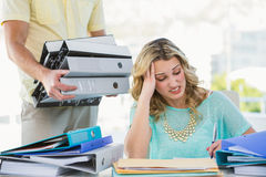 Stressed creative businesswoman with stack of files Stock Images
