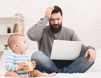 Stressed dad trying to work and watching for baby stock image