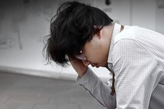 Stressed depressed young Asian business man covering face with hands. Royalty Free Stock Photography