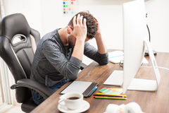 Stressed designer at his office desk Stock Photography