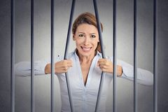 Stressed desperate angry businesswoman bending bars of her prison. Cell grey wall background. Life limitations, law violation infringement tax evasion royalty free stock photo