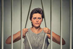Stressed desperate sad woman bending bars of her prison cell. On grey wall background. Life limitations, law violation consequences concept. Face expression royalty free stock photography