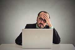 Stressed displeased business man working on laptop computer. Portrait mature stressed displeased worried business man sitting in front of laptop computer royalty free stock photography