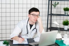 Stressed doctor in clinic under pressure. Malpractice, treatment error and mistake or negligence. Workplace bullying.  royalty free stock photos