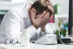 Stressed doctor cover face under pressure. Sad nurse, tired physician or upset doc. Medic crying in hospital office. Malpractice, treatment error and mistake stock images