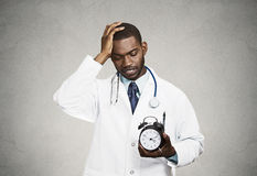 Stressed doctor holding alarm clock Stock Images