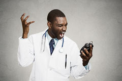 Stressed doctor, holding alarm clock Royalty Free Stock Photography