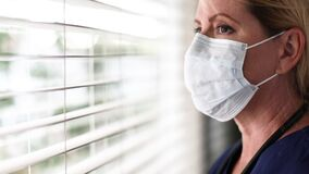 Stressed Doctor or Nurse On Break At Window Removing PPE, Face Mask and Protective Glasses