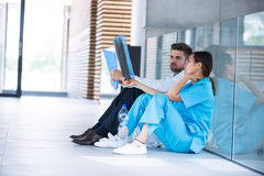 Stressed doctor and nurse sitting on floor examining X-ray report Stock Photo