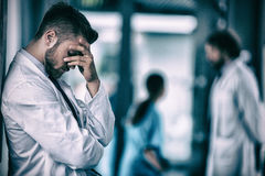 Stressed doctor standing against wall in hospital Stock Photo