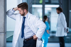 Stressed doctor standing in hospital Stock Image