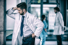 Stressed doctor standing in hospital Stock Photography