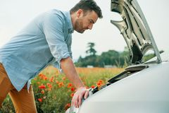 Driver in trouble after vehicle breakdown waiting for help. Stressed driver after car breakdown calling roadside service royalty free stock image